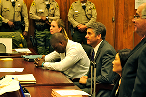 Brian Banks sits at a table in court with Alissa Bjerkhoel and Justin Brooks