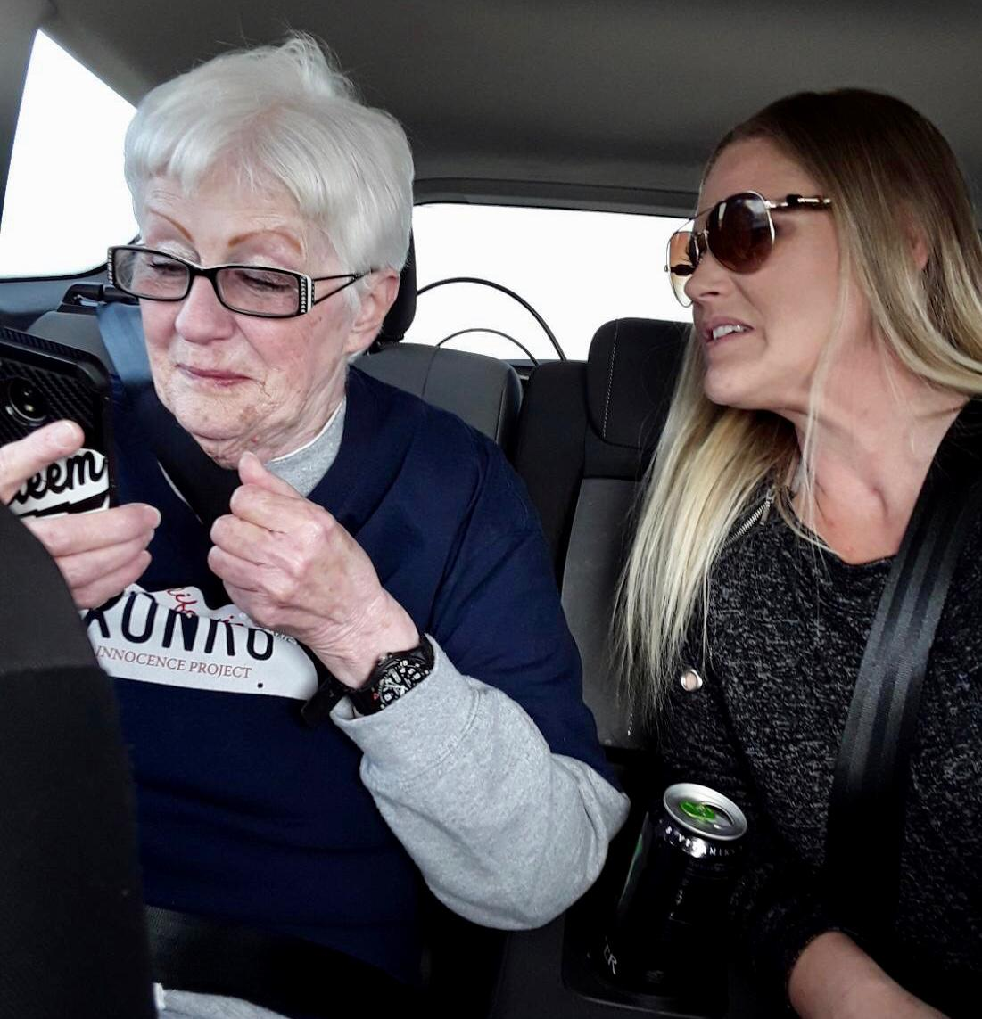 Suzanne Johnson looks at a cell phone as she drives away from a prison.