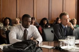 Brian Banks (played by Aldis Hodge) and Justin Brooks (played by Greg Kinnear) sit in a courtroom.